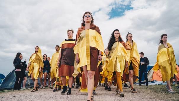 Mit gelben Flickentüchern bekleidete Menschengruppe marschiert in V-Formation auf den Betrachtenden zu