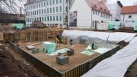 Baustelle mit Fundament, auf dem drei Bauarbeiter tätig sind