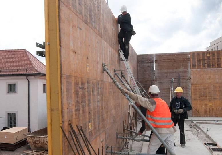 Drei am Rohbau einer Wand beschäftigte Bauarbeiter