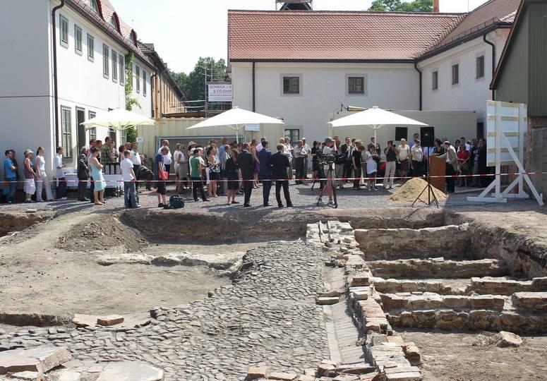 Im Vordergrund eine Baustelle, um Hintergrund um ein Rednerpult versammelte Menschenmenge