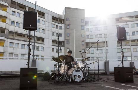 Ein Mann spielt Schlagzeug mit Soundanlage, im Hintergrund ist eine Plattenbau-Siedlung