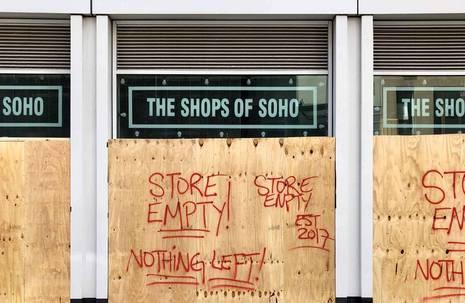 """Ladenzeile mit Aufschrift """"The Shops of Soho"""", von Bauzäunen mit Graffiti-Sprüchen """"Store empty! Nothing left!"""" versperrt"""