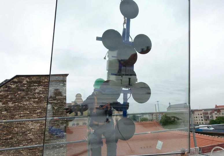 Eine an Noppen befestigte Glasscheibe wird von einem Bauarbeiter festgehalten