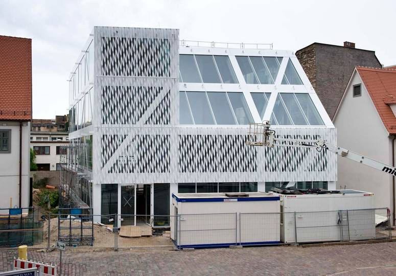 Gebäude mit weißer gemusterter Fassade, davor Baucontainer