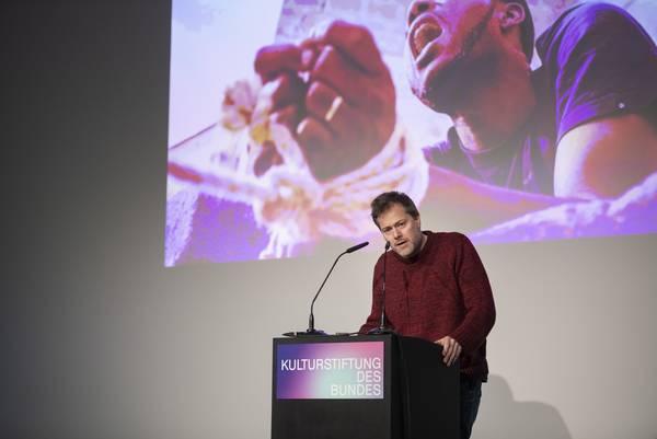 Mann am Rednerpult, hinter ihm Leinwand mit Foto von Mann mit gefesselten Händen