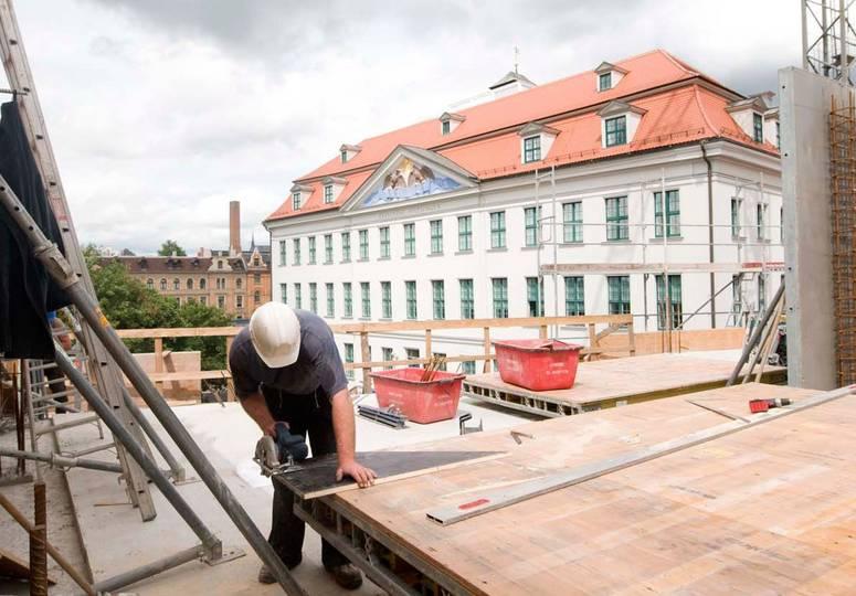 Ein Bauarbeiter schneidet ein Brett auf dem Rohbau, im Hintergrund ein weißes Gebäude