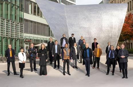 Personengruppe posiert im Freien vor einer großen künstlerischen Metallplatte