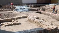 abgesperrte Baustelle mit Mauerfundamenten im Boden, im Hintergrund Personen in Latzhosen