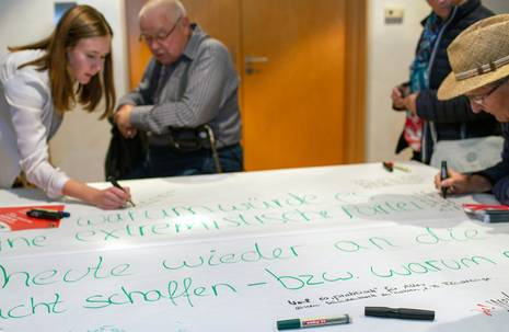 Vier Menschen schreiben Stichworte auf einen großen Bogen Papier