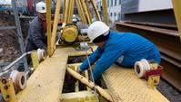 Zwei Bauarbeiter arbeiten an einem gelben Stahlgerüst