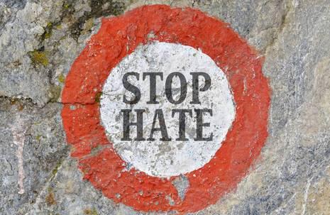 """Ein gespraytes Warnschild mit der mittigen Beschriftung """"Stop Hate"""" auf einer Beton- oder Asphaltoberfläche"""