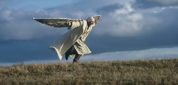 Weiß gekleideter Mann mit gebastelten Flügeln rennt einen Hügel hinauf, Wolken im Hintergrund