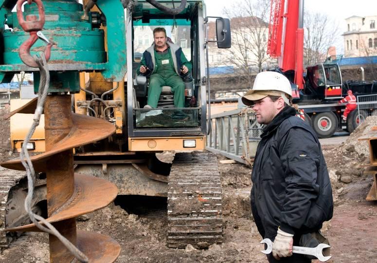Ein Bauarbeiter begutachtet eine große Bohrschraube, im Hintergrund ein Mann im Baufahrzeug