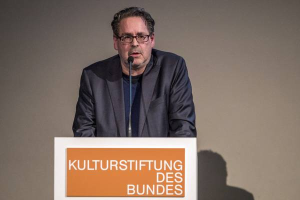 """Ein Mann am Rednerpult mit der Aufschrift """"Kulturstiftung des Bundes"""""""