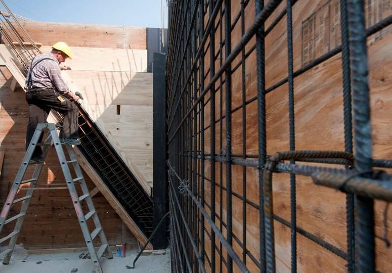 Sich im Bau befindende Gebäudewand, im Hintergrund Bauarbeiter auf einer Leiter