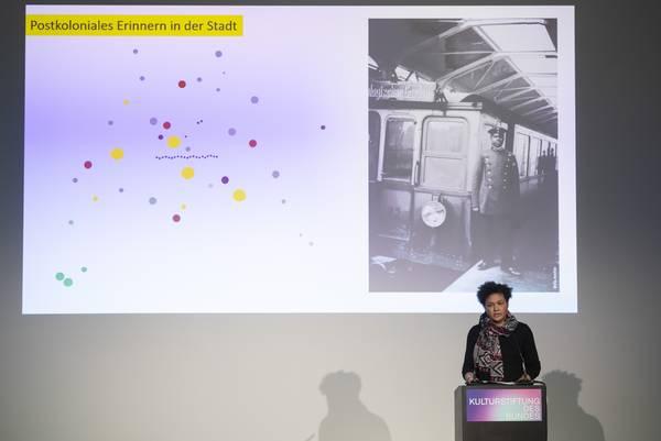 """Frau am Rednerpult, hinter ihr Leinwand mit Aufschrift """"Postkoloniales Erinnern in der Stadt"""""""