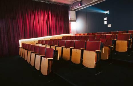 Kinosaal mit rot bezogenen Holzsitzen und rotem Vorhang