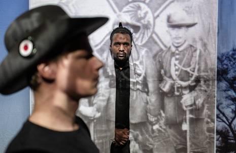 Mann blickt durch einen Vorhang mit aufgedruckter Fotografie von Soldaten