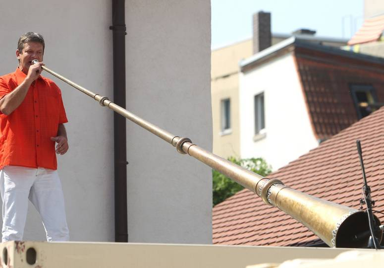 Ein Mann auf einer Bühne spielt auf einem langen Horn