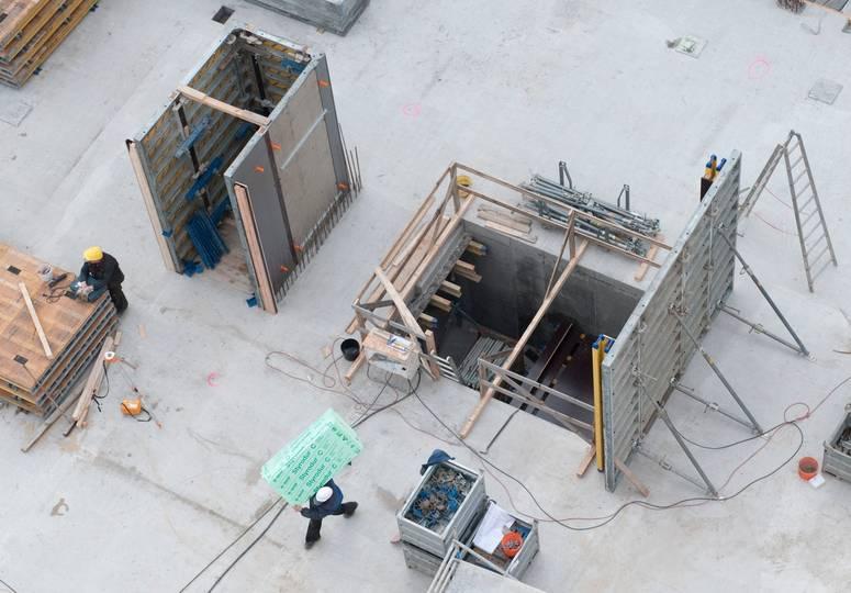 Vogelperspektive auf Rohbau mit zwei Bauarbeitern