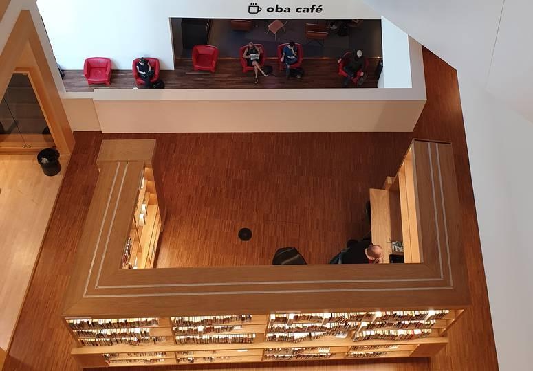Vogelperspektive auf hölzernen Raum mit Bücherregal und Café hinter Trennwand