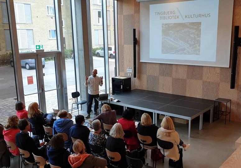 Mann hält Präsentation über die Tingbjerg Bibliotek vor einer Gruppe