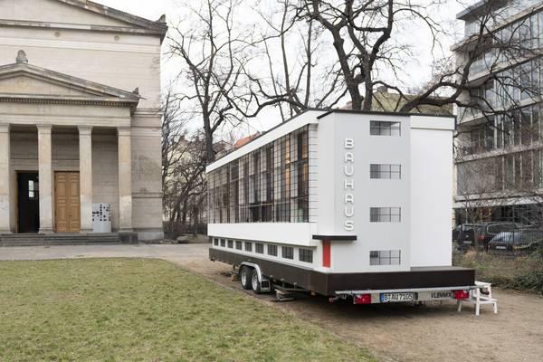 """Ein Gefährt, auf dem ein Miaturgebäude mit Aufschrift """"Bauhaus"""" steht"""