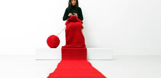 Eine Frau sitzt in einem weißen Raum auf einem Podest und strickt an einem langen roten Schal