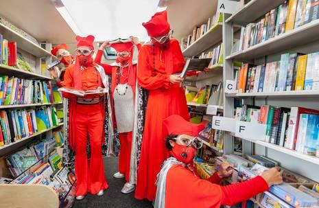 Fünf Personen in roter Kleidung sowie mit Mundschutz, Hüten und übergroßen Brillen in Bücherei