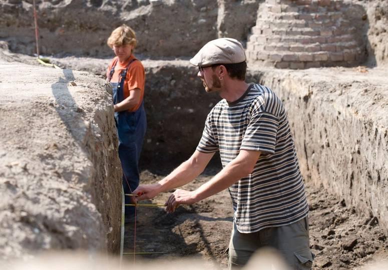 Mann und Frau arbeiten mit Schnur und Hölzern in einem Graben der Baustelle