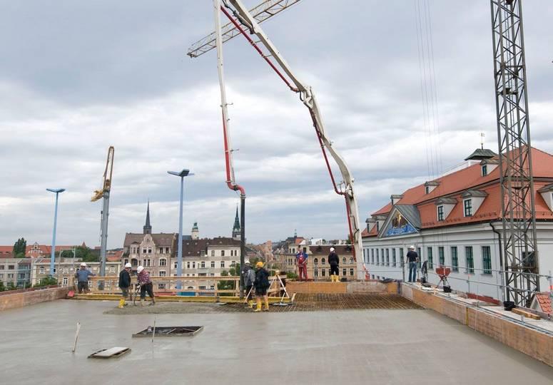 Mehrere Bauarbeiter auf dem Rohbau eines Dachs, im Hintergrund ein weißer Kran mit langem Rohr