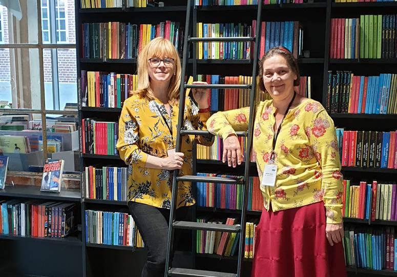 Zwei Frauen stehen an Leiter vor Bücherregal und lächeln in die Kamera