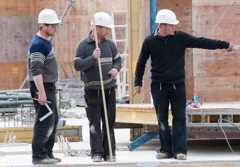 Drei Bauarbeiter im Gespräch, einer zeigt nach rechts