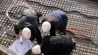 Vogelperspektive auf drei Bauarbeiter, die über etwas gebeugt sind