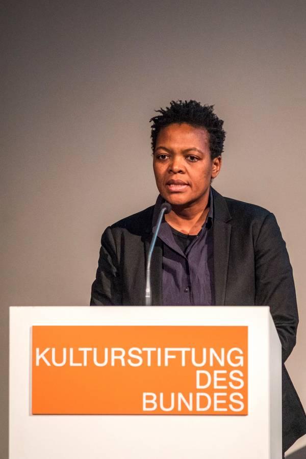 """Eine Frau am Rednerpult mit der Aufschrift """"Kulturstiftung des Bundes"""""""
