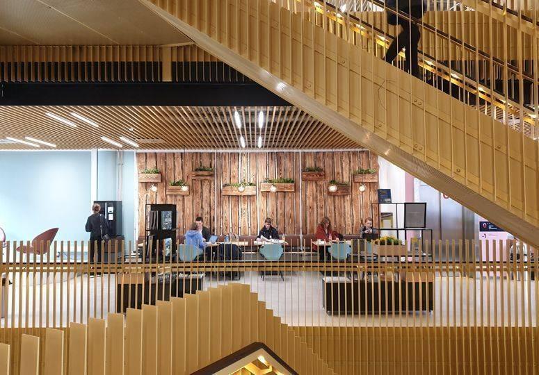 Moderner Saal mit Sitzgelegenheiten und Treppe ins Obergeschoss