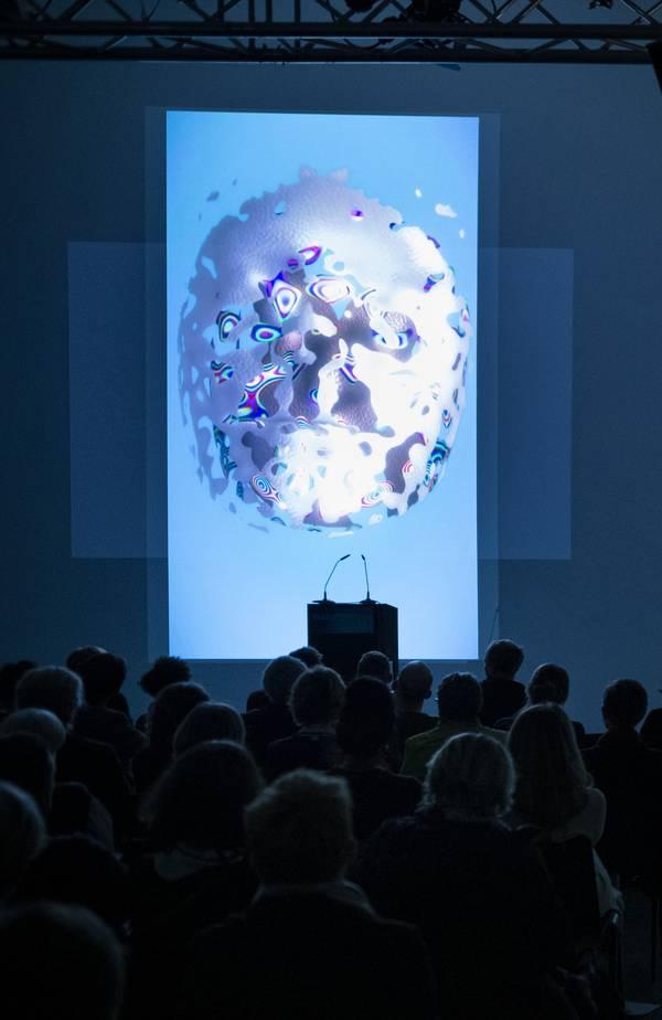 Dunkel gehaltene Menschenmenge blickt auf blaue Leinwand mit weiß strukturiertem Kreis