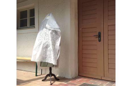 Beigefarbene Hauswand mit hölzerner Tür, davor steht auf Fliesen ein mit weißer Plane verhüllter Kleiderständer