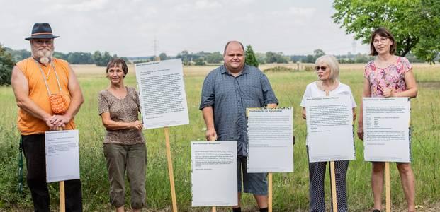 Fünf stehende Personen mit weißen Texttafeln vor sich, im Hintergrund ein Feld