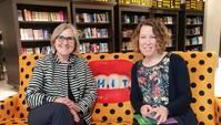 Zwei Frauen auf Sofa lächeln in die Kamera, im Hintergrund Bücherregale