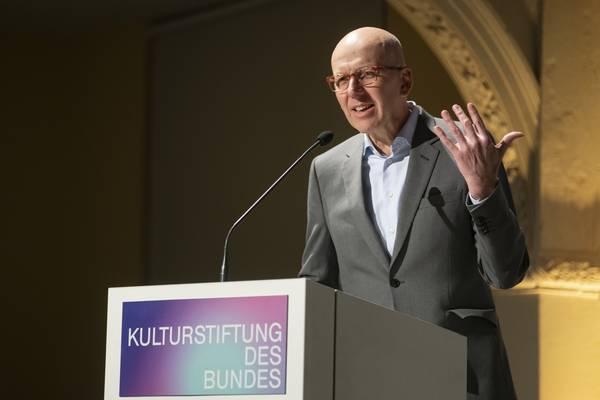 """Ein gestikulierender Mann am Rednerpult, darauf die Aufschrift """"Kulturstiftung des Bundes"""""""