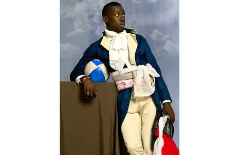 Mit Jackett bekleideter schwarzer Mann mit Fußball unter dem Arm blickt in die Ferne