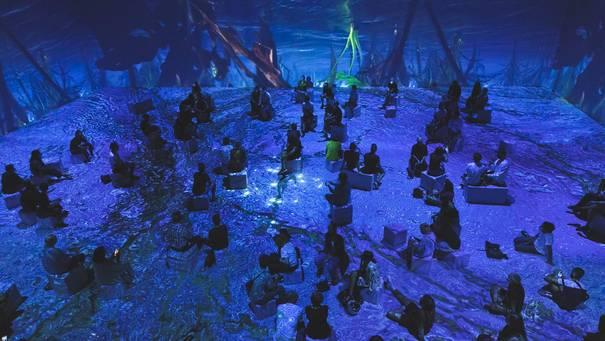 Menschen auf Hockern in Raum, der mit blauer 3D-Projektion des Meeres bestrahlt wird