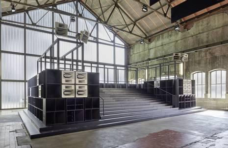 In einer Werkhalle stehende Bühnenvorrichtung, zu der Treppenstufen hoch führen