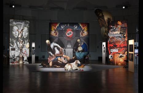 Drei Bildschirme in dunkler Halle mit abstrakten Szenen, im Vordergrund Installation von drei gemalten Männern mit Hund