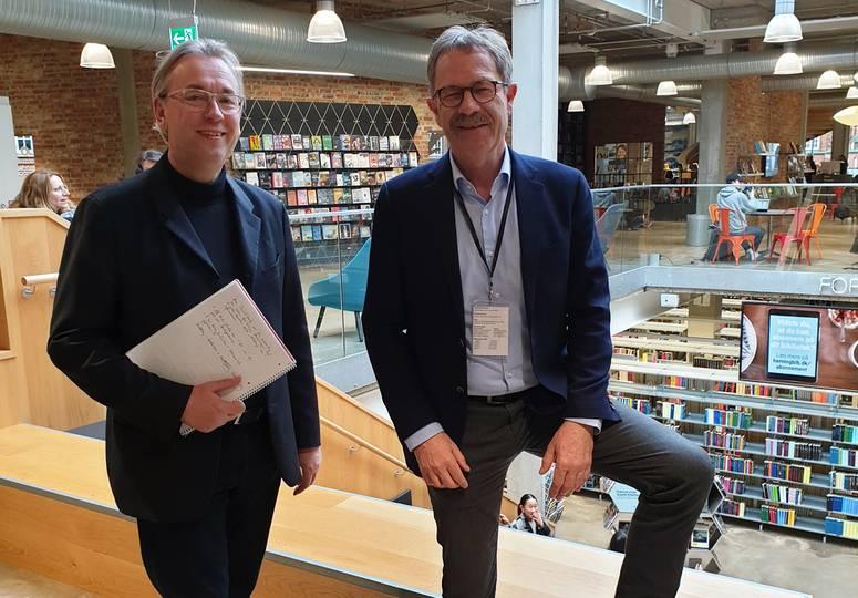 Zwei Männer im oberen Stockwerk einer Bibliothek lächeln in die Kamera
