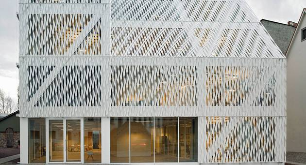 Zu sehen ist eine Frontansicht des Neubaus der Kulturstiftung des Bundes in Halle an der Saale, ein geometrisches modernes Gebäude mit weißer, Relief-artiger Fassade