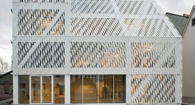 Frontansicht eines geometrisch modernen Gebäudes mit weißer reliefartiger Fassade