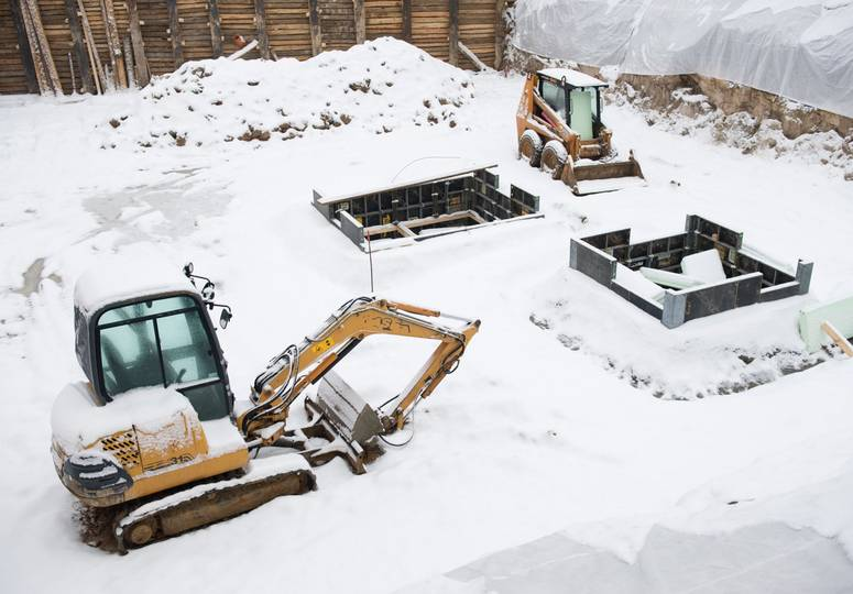 Mit Schnee bedeckte Baustelle, auf der zwei eingeschneite Baufahrzeuge stehen