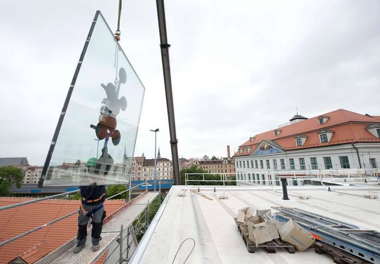 Eine große an einem Kran befestigte Glasscheibe wird von einem Bauarbeiter festgehalten